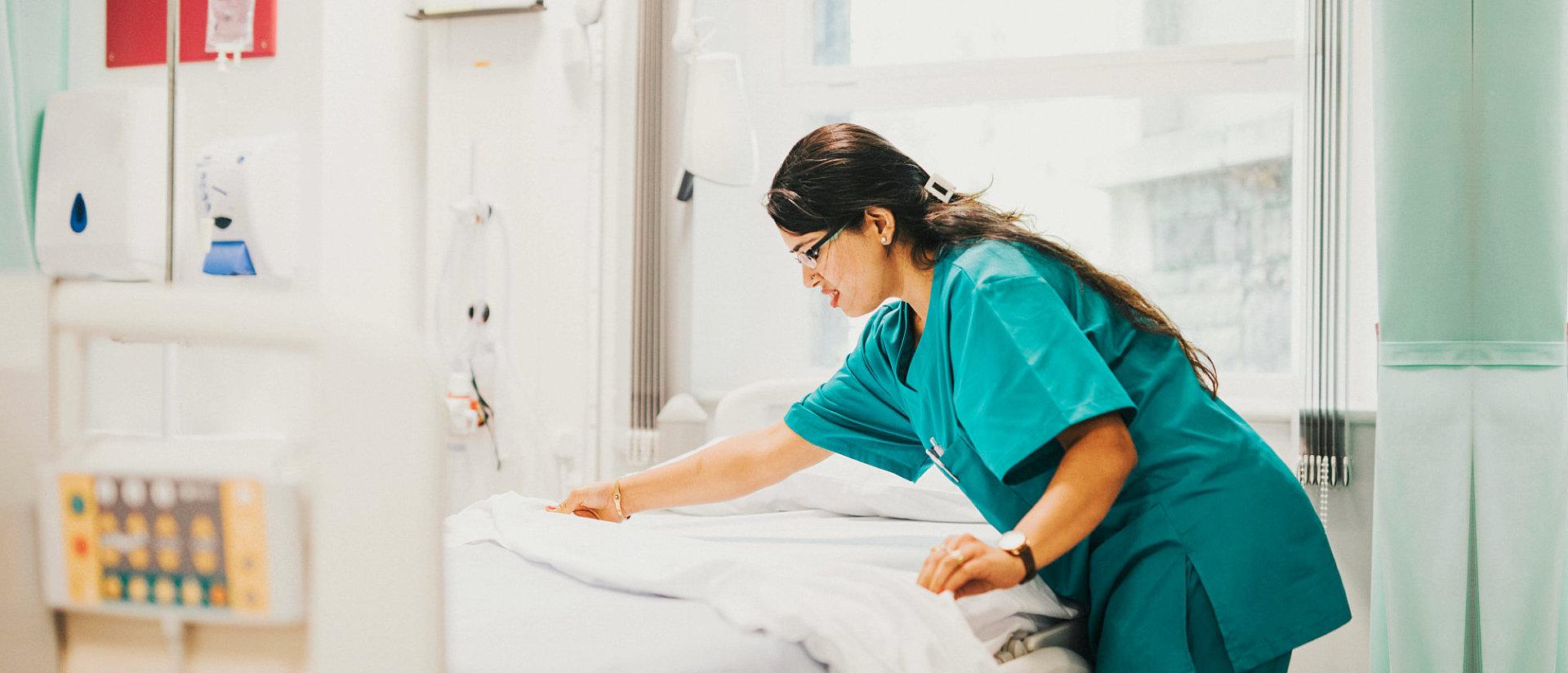 nurse folding bed sheet