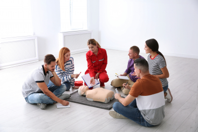 group of people with instructor at first aid class indoors